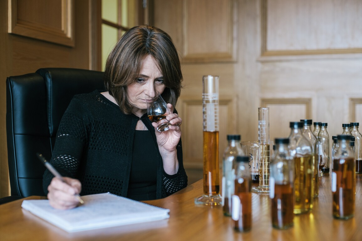 Woman smelling whisky while writing in notebook