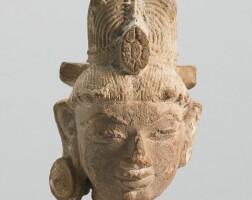 1306. a buff sandstone head of a deity western india, 10th / 11th century