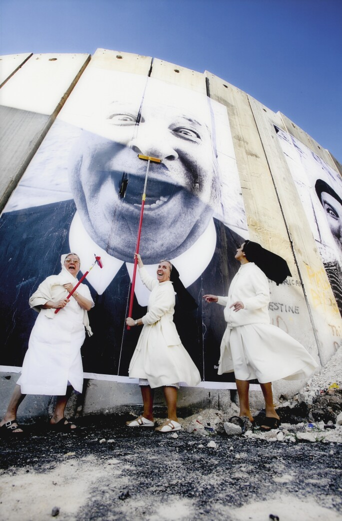 Three nuns paste a giant photograph of a man's face on a wall in Palestine