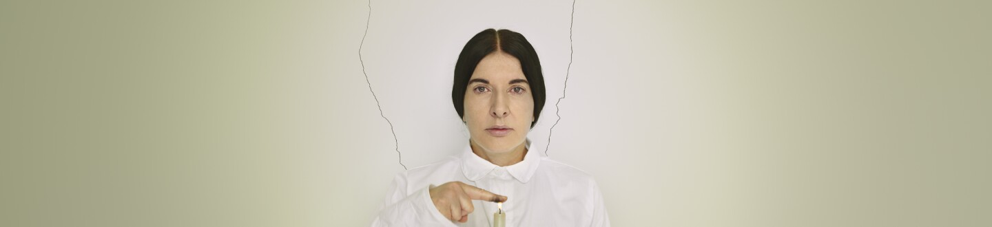 Marina Abramovic dressed in all white holds her finger, covered in soot, over a lit green candle.