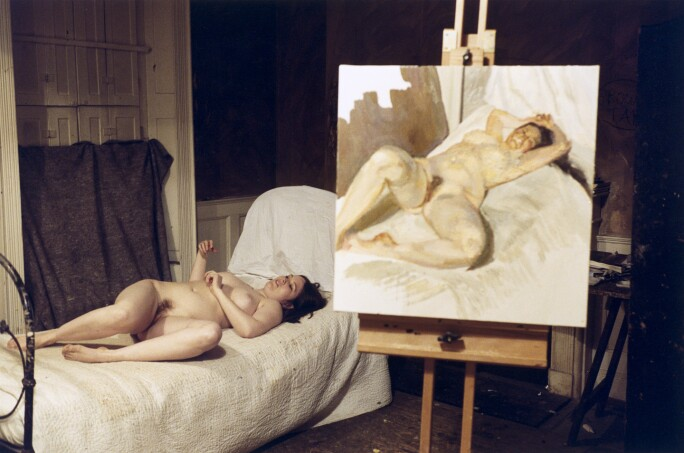 A nude white woman with dark hair reclines on a bed with dirty white sheets. A painting of her is on an easel to the right of the bed.