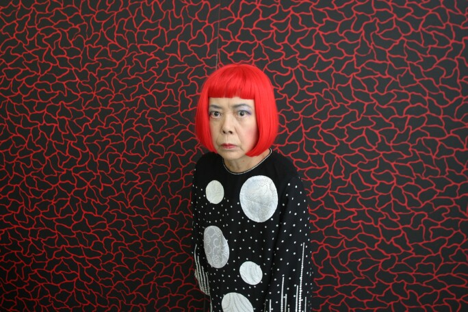 Japanese artist Yayoi Kusama stands in front of one of her paintings in her studio, Tokyo, Japan