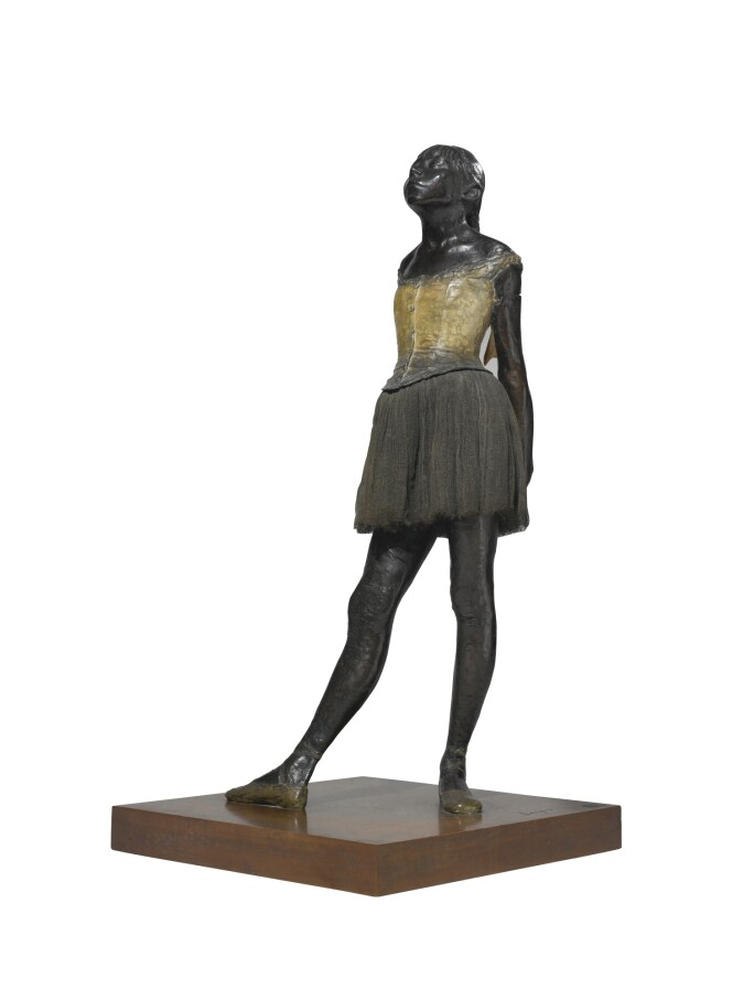 Sculpture of a dancer with her hands clasped behind her back.