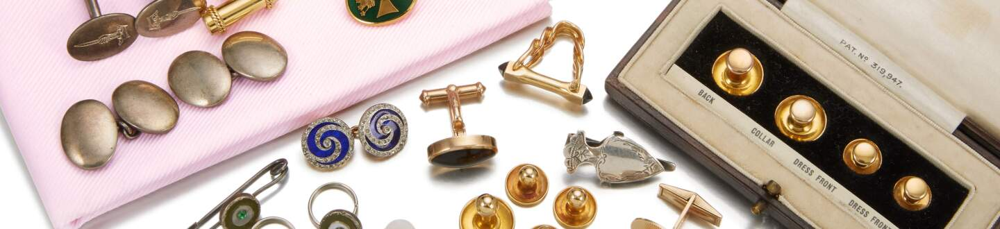 A collection of cufflinks and dress accessories in an auction selling men's accessories