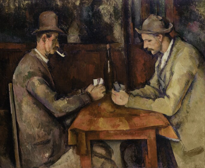two men sitting at a table playing cards