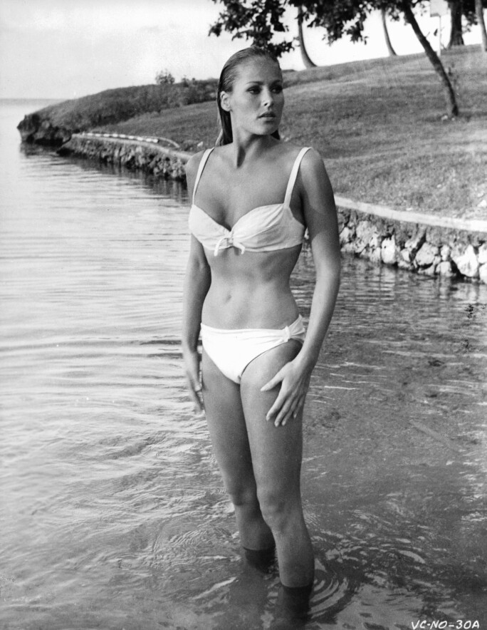 Ursula Andress In 'James Bond: Dr. No' emerging from water, wearing a white bikini.