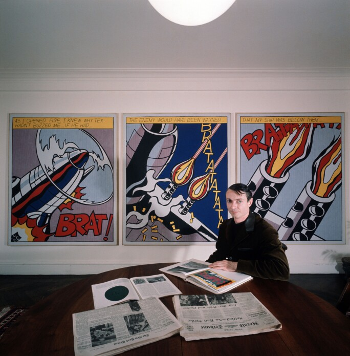 The American painter and exponent of Pop Art, Roy Lichtenstein, is sitting at a table and is attentively looking through some magazines; over his shoulder some of his artwork. 1964.