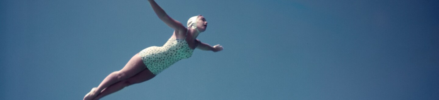 1950s WOMAN WEARING WHITE ONE PIECE BATHING SUIT AND CAP SWAN DIVING OFF HIGH BOARD AGAINST BLUE SKY