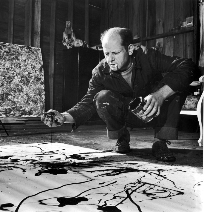 Painter Jackson Pollock, cigarette in mouth, dropping paint onto canvas.