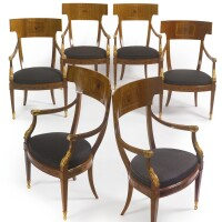 6. a set of six north european neoclassical style parcel-gilt and ebony-inlaid mahogany armchairs