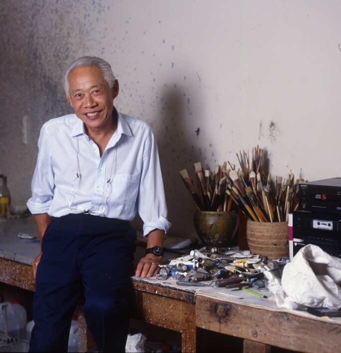 Zao Wou-ki in his studio with paints and paintbrushes on the table behind him.