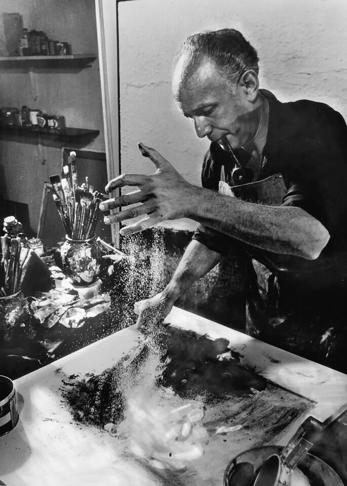 Abstract painter Enrico Donati working w. dust, auto paint, pipe ashes, etc. to create one of his paintings.