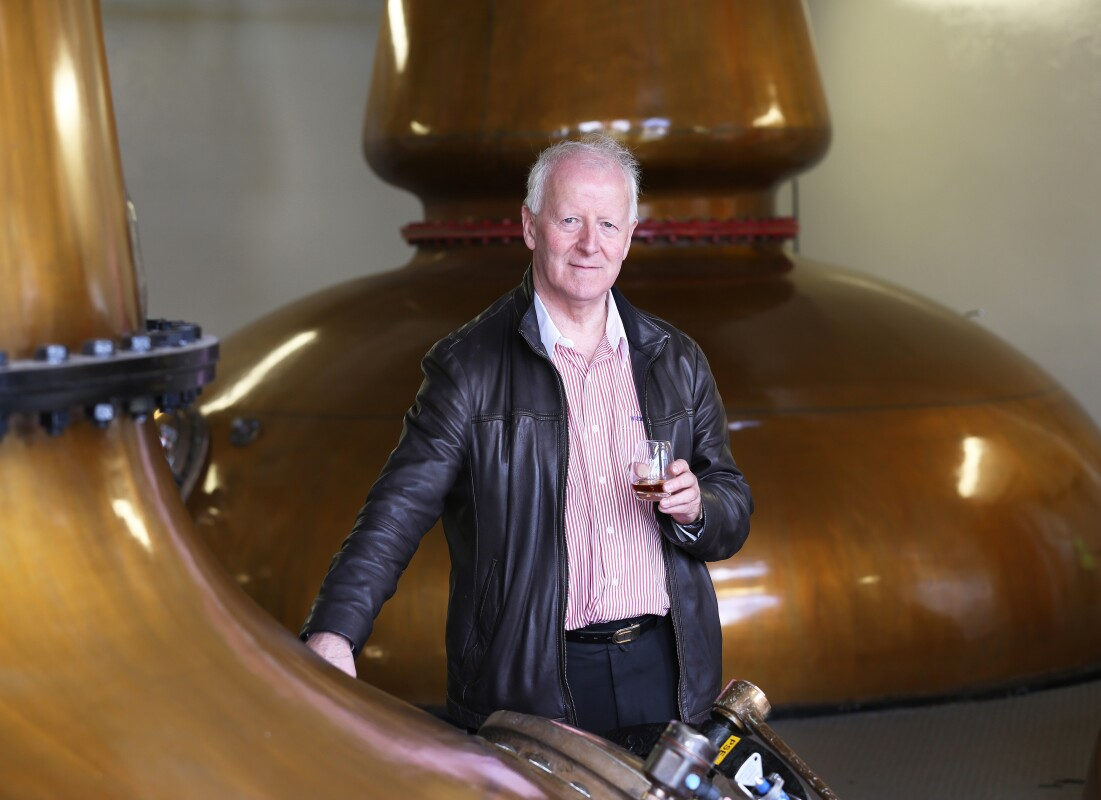 Man holding glass of whisky while standing inside a whisky distillery