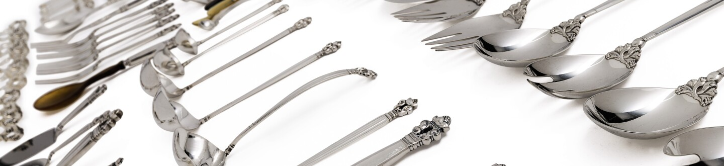 A group of Georg Jensen silverware in an auction selling silver flatware by Jensen