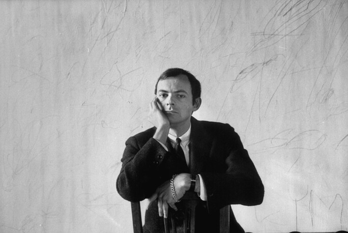 Black-and-white photograph of artist Cy Twombly from 1958, wearing a suit and tie and sitting backwards on a chair. His righthand rests on his face.