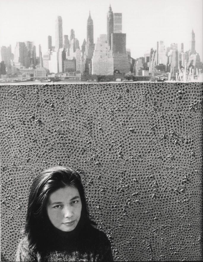 Yayoi Kusama standing with her work against a background of Manhattan, NY in 1961. Courtesy YAYOI KUSAMA Inc.