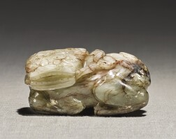 214. a pale celadon and brown jade 'buddhist lion' ming dynasty  