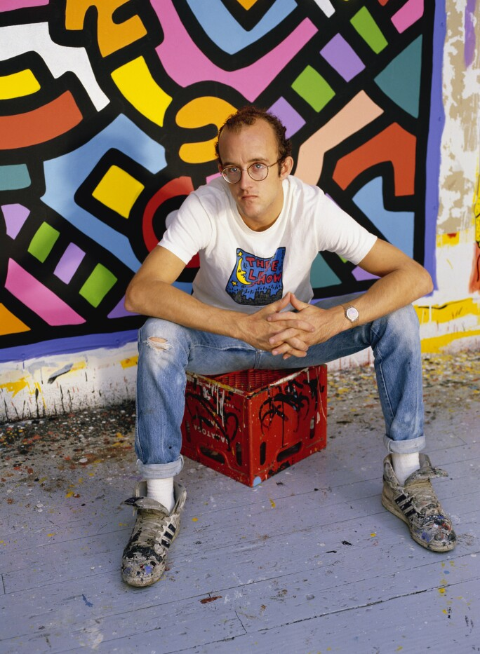 Keith Haring seated on a milk crate in front of a canvas.