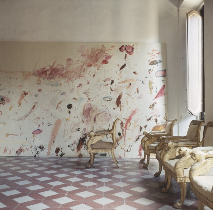 Room in the Rome apartment of artist Cy Twombly featuring a row of French Empire chairs and one of Twombly's paintings leaning against the back wall.