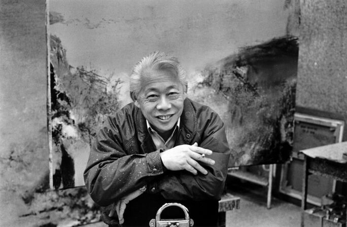 Zao Wou-Ki smoking a cigarette in his studio, seated before one of his canvases.